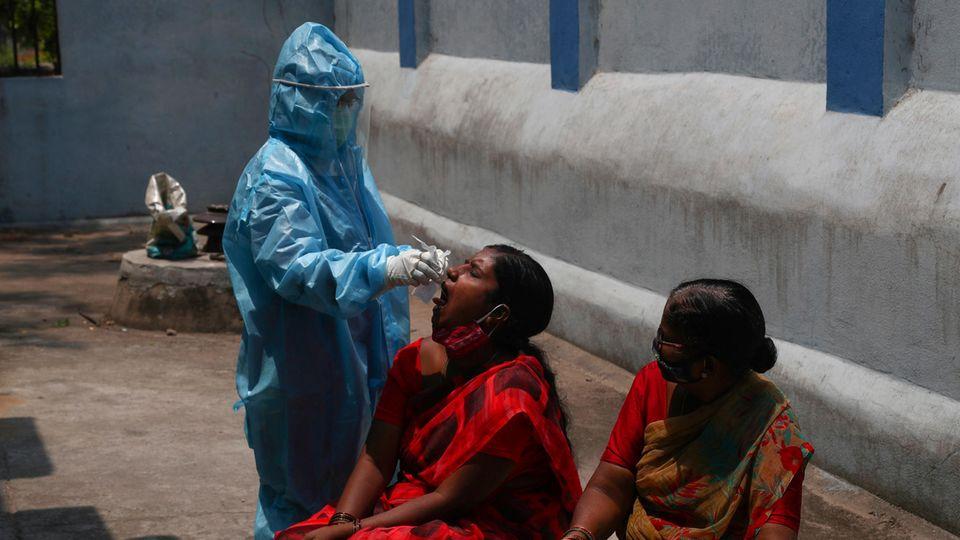 Indien Coronavirus: Ein Mitarbeiter des Gesundheitswesens nimmt einer Frau einen Mundabstrich ab