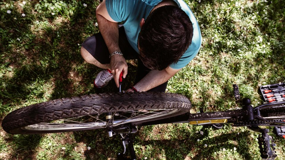 Fahrrad-Werkzeug: Junger Mann kniet mit Werkzeug neben seinem Mountainbike