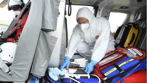 Ein Arzt in weißem Schutzanzug bereitet seine Ausrüstung im Intensivtransporthubschrauber auf einen Corona-Patienten vor