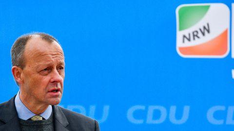 Ein weißer Mann mit kurzen braunen Haaren spricht vor einer blauen Wand mit CDU NRW Logo in zwei Mikrofone