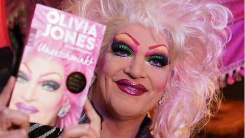 """Dragqueen Olivia Jones trägt eine blonde Perücke mit rosa Strähnen und hält ihr Buch """"Ungeschminkt"""" neben ihr Gesicht"""