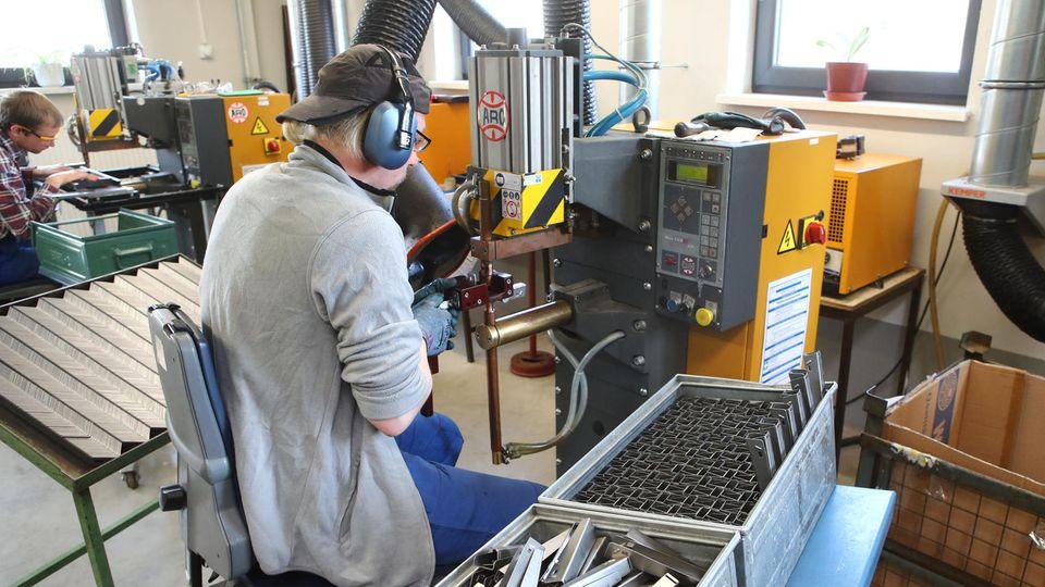 Zwei Personen arbeiten in einer Werkstatt für Menschen mit Behinderung