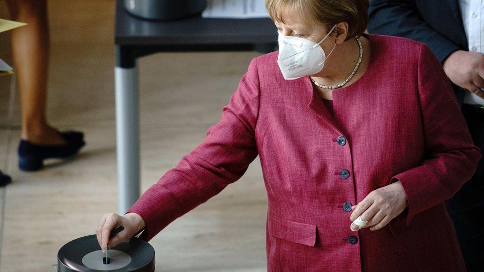 Bundeskanzlerin Angela Merkel (CDU) steckt ihre Stimmkarte bei der Sitzung des Bundestags in die Wahlurne