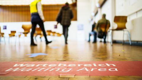 Rheinland-Pfalz, Mainz: Menschen gehen im Impfzentrum der Landeshauptstadt in den Wartebereich