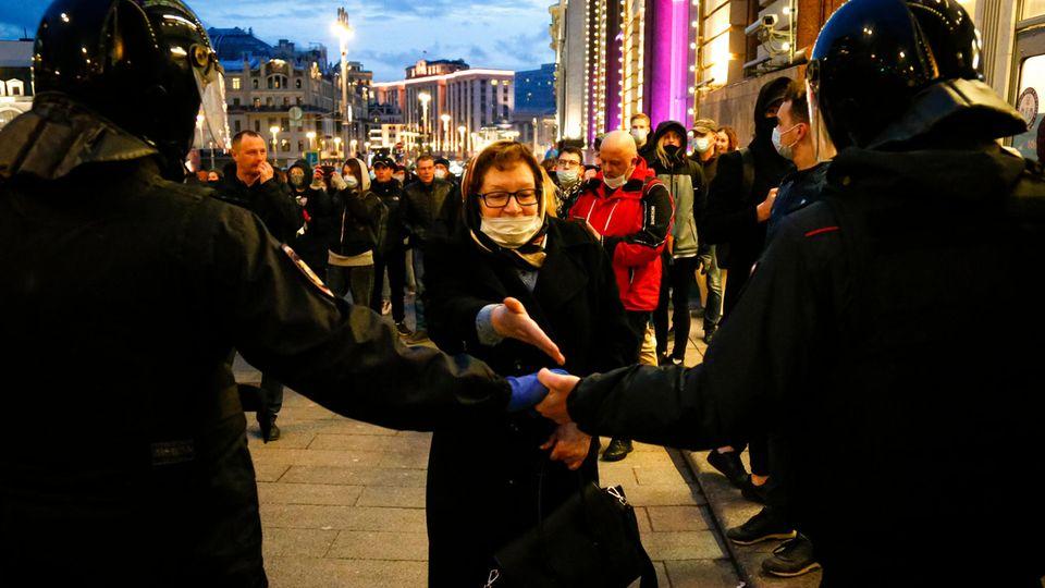 Russland, Moskau: Eine Frau gestikuliert vor Bereitschaftspolizisten