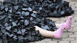Eine kleine Schaufensterpuppe liegt symbolisch unter Kohle begraben