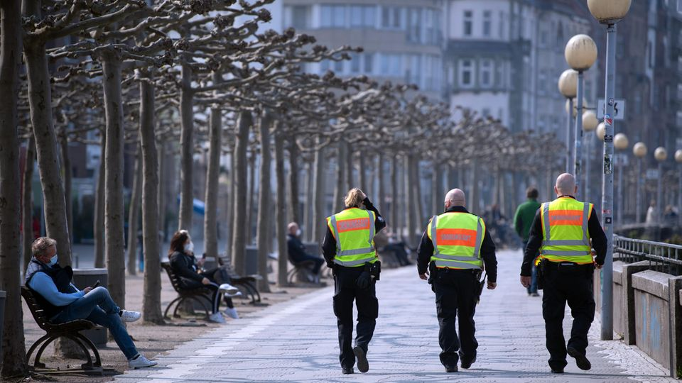 Mitarbeiter des Ordnungsamtes gehen am Düsseldorfer Rheinufer entlang, um die Maskenpflicht zu überprüfen