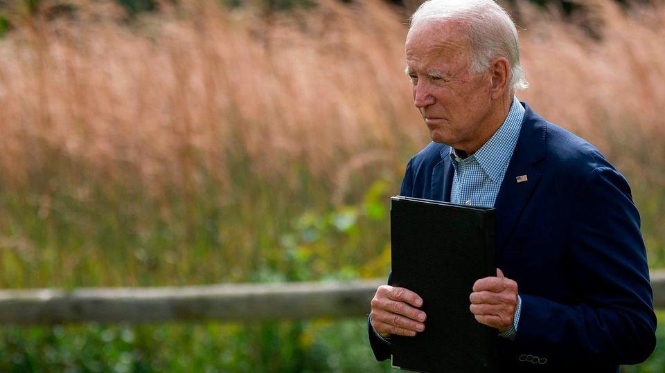 Joe Biden mit einer Kladde in der Hand vor einem Kornfeld