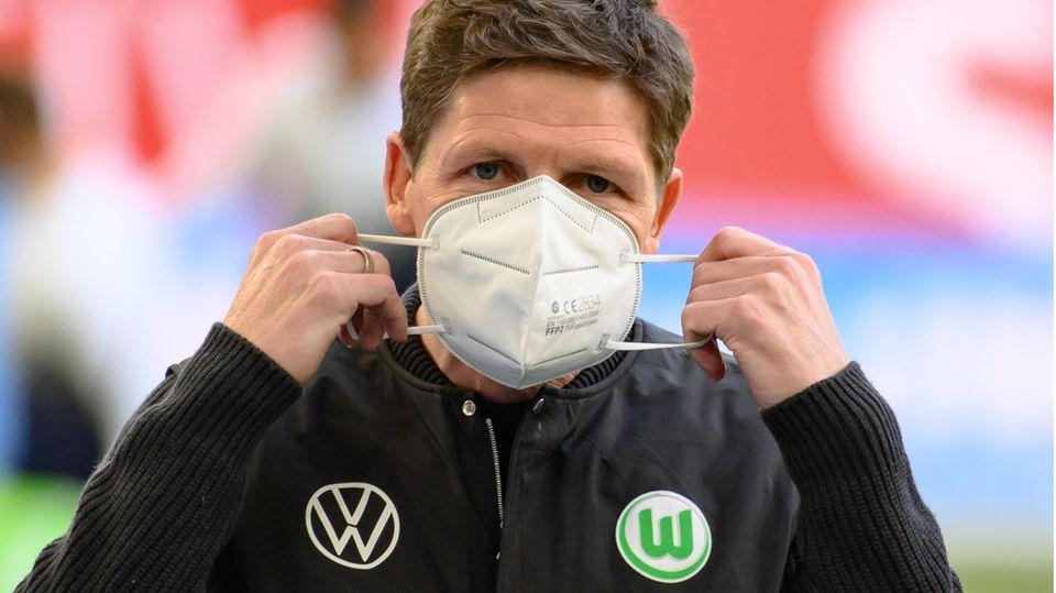 Ein weißer Mann mit dunkelblondem Seitenscheitel setzt sich eine FFP2-Maske auf und hat dafür seine Hände an beiden Gummibändern