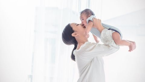 Mutter hält ihr Baby hoch und gibt ihm einen Kuss auf die Wange