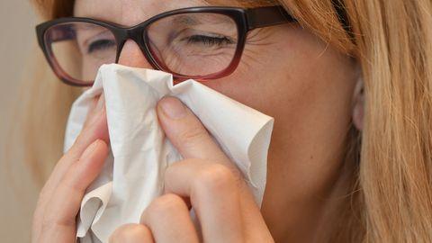 Eine Frau putzt sich die Nase mit einem Taschentuch