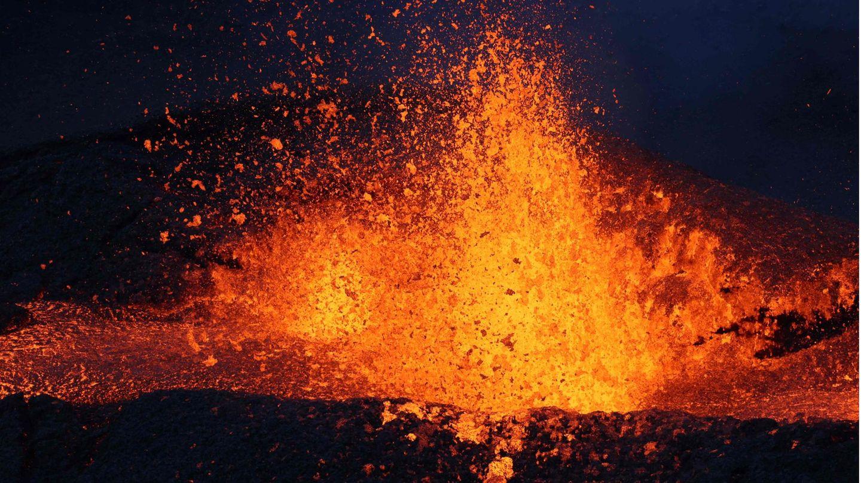 Im Dunkeln fliegt ein Schwall Lava aus einem Vulkankrater