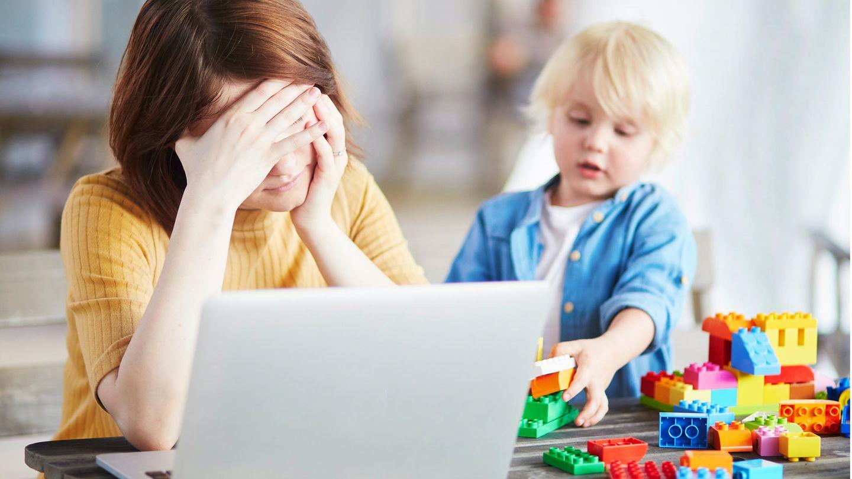 Frau sitzt vor genervt und erschöpft vor dem Laptop, während ihr Kind neben ihr auf dem Tisch mit LEGO-Steinen spielt