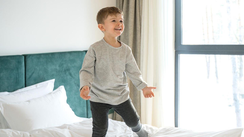 Ein kleiner Junge steht gut gelaunt im Bett und ruft etwas