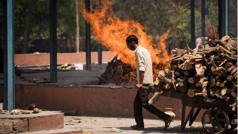 Während im Hintergrund ein Einäscherungsfeuer brennt, zieht ein Arbeiter in hellem Hemd einen Karren mit Holzscheiten vorbei