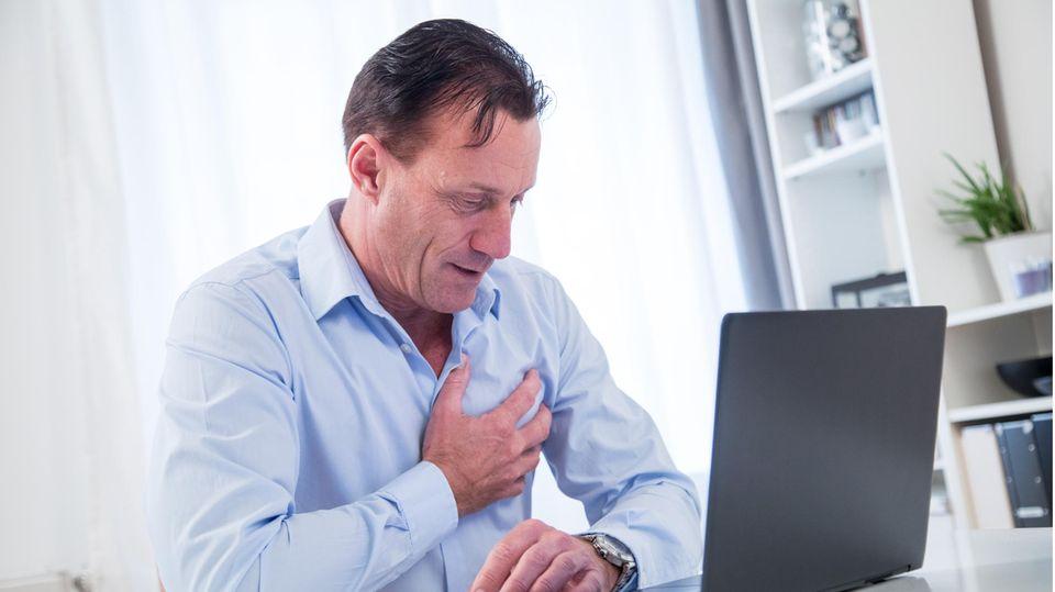 Ein Mann sitzt am Laptop und greift sich an die Brust