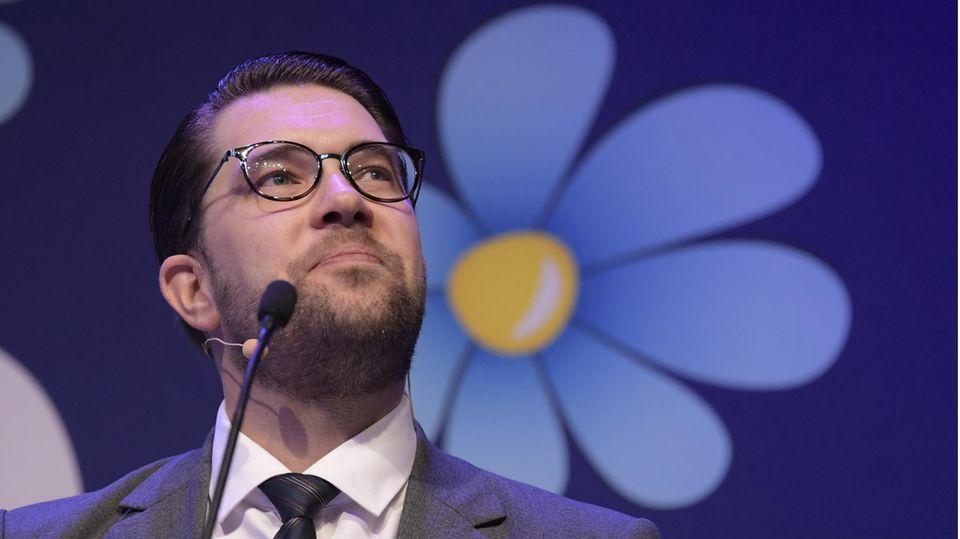 Der Parteivorsitzende der Schwedendemokraten, Jimmie Åkesson, vor dem Logo seiner Partei, einer blau-gelben Blume