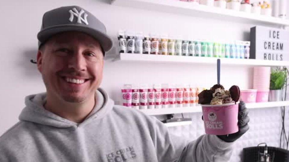 """Ein junger Mann in grauem Kapuzenpulli und """"NY""""-Cap lächelt, während er mit links einen vollen rosa Papp-Eisbecher hochhält"""