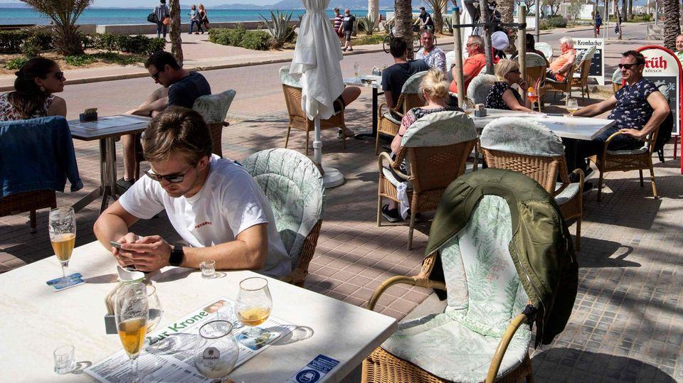 Auf der Terrasse eines Restaurant sind alle Tische besetzt. Die Gäste sitzen in der Sonne. Hinter ihnen Palmen, Strand und Meer