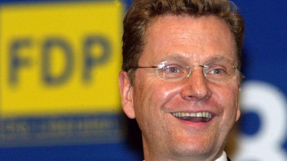 Guido Westerwelle im FDP-Logo im Hintergrund