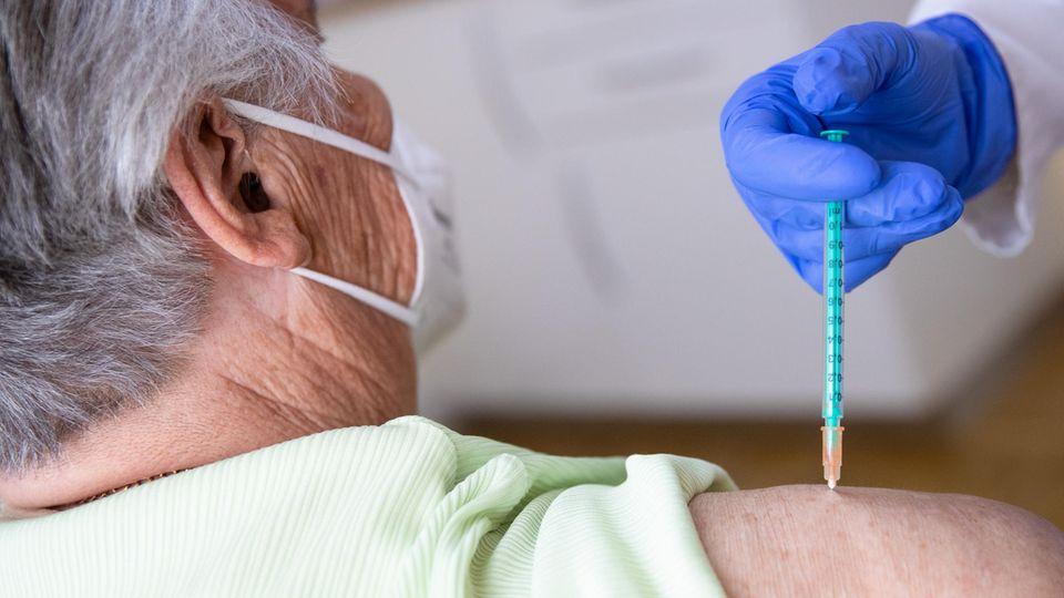 Eine Fachärztin für Allgemeinmedizinimpft in ihrer Praxis eine Patientin gegen das Coronavirus