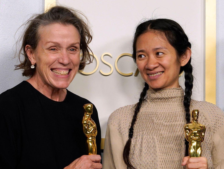 """Die beiden großen Gewinnerinnen des Abends strahlen hinterher um die Wette: Frances McDormand undChloéZhao gewannen beim wichtigsten Filmpreis des Jahres je zwei Oscars. Zunächstwar McDormand als beste Schauspielerin, Zhao als beste Regisseurin für """"Nomadland"""" ausgezeichnet worden. Als Krönung wurde das Roadmovie zum bestenFilm gekürt - und als Prodzentinnen nahmen McDormand und Zaho ihre zweite Trophäe entgegen."""