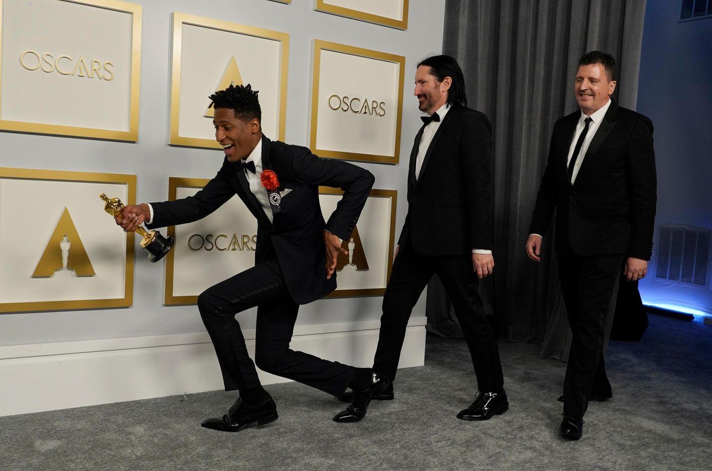 """Jon Batiste, Trent Reznor und Atticus Ross (v.l.) zelebrieren ihren Oscar-Gewinn in der Kategorie beste Filmmusik. Sie steuerten den Soundtrack für den Animationsfilm """"Soul"""" bei. Für Reznor und Ross ist es bereits der zweite Oscar: Die beiden wurden 2011 für ihren musikalischen Beitrag zu """"The Social Network""""ausgezeichnet."""