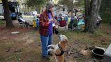 """Woodbine, USA. Auf einem Campingplatz in einem Pinienwald belohnt eine Frau ihren Hund. Sie gehört zu einer Gruppe, die sich Rving Women nennt. Das sind Frauen, die ausschließlich in ihren Campern leben und von einem Ort zum nächsten ziehen - als Nomaden. Viele sind bereits im Ruhestand, andere arbeiten noch. Ihre Art zu Leben wird in dem Film """"Nomadland"""" porträtiert, der gerade mit drei Oscars ausgezeichnet wurde."""