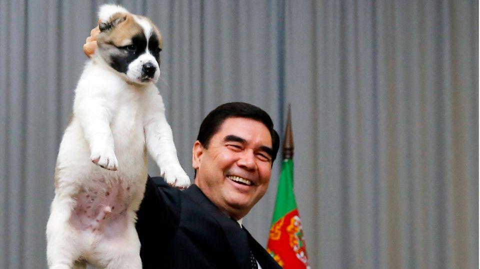 Turkmenistans Präsident Kurbanguly Berdymukhanmedov hält einen jungen Schäferhund am Nacken in die Höhe