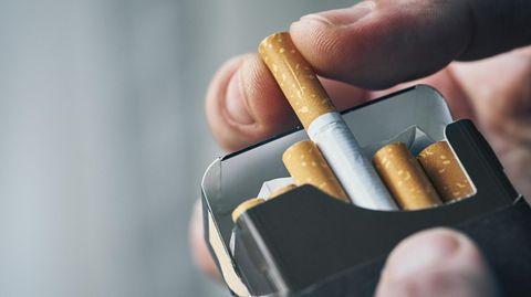 Mann holt Zigarette aus der Schachtel