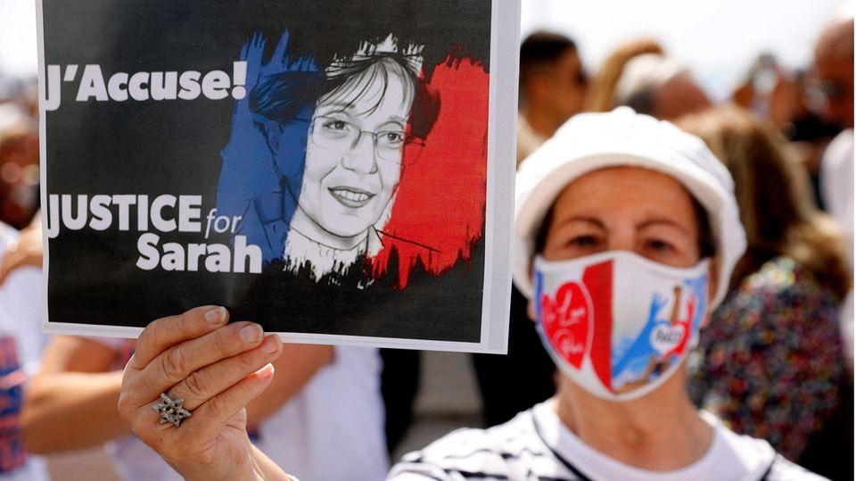 Eine Frau mit Mund-Nasen-Schutz in den französischen Nationalfarben hält auf einer Demo hält ein Schild mit Forderungen hoch