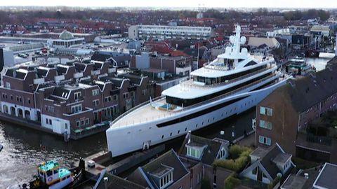 Schlepper ziehen riesige Luxus-Jacht durch winzige Kanäle in den Niederlanden