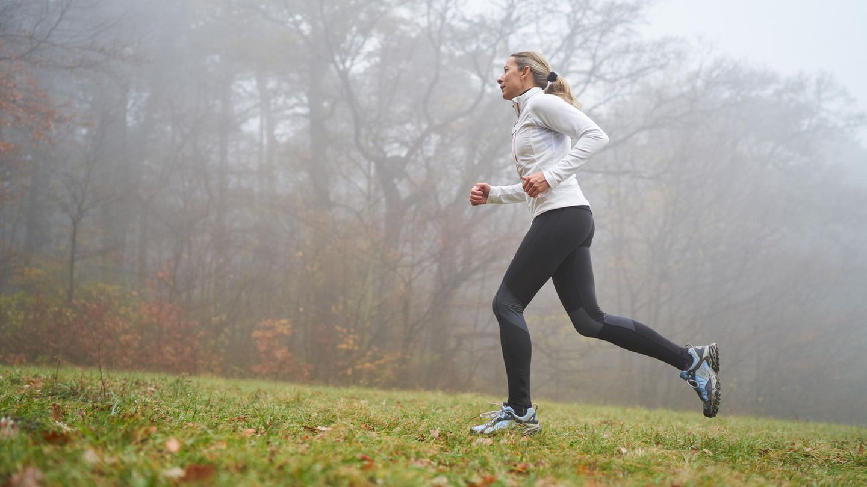 Eine Joggerin läuft bergan im Regen und bei Kälte