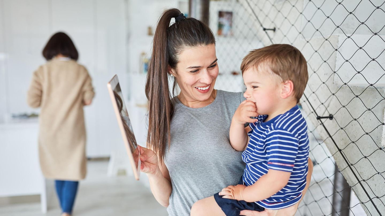 Eine junge Frau hält ein Kleinkind auf dem Arm, im Hintergrund geht eine weitere Frau weg