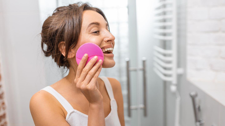 Frau nutzt elektrische Gesichtsbürste