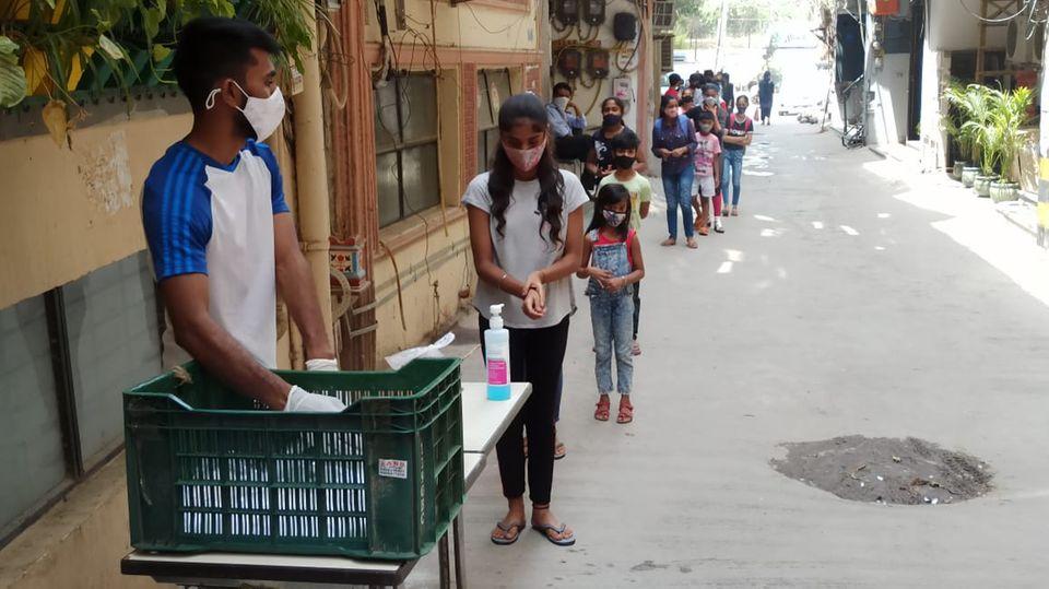Die Kinder stehen Schlange, um vom Sunshine Project mit Masken und Seife versorgt zu werden