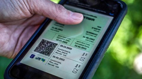 """Ein israelischer Mann hält ein Smartphone in der Hand, auf dem der sogenannte """"Grüne Pass"""" abgebildet ist"""