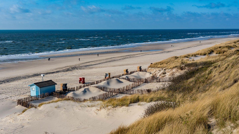 In der Vorsaison in den Dünen auf Sylt:Vereinzelte Strandbesucher laufen am Strand der Nordsee entlang.