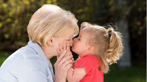 Kleines Kind gibt seiner Großmutter einen Kuss.
