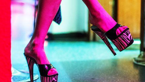 Frauenbeine mit High Heels werden von rotem Licht angestrahlt