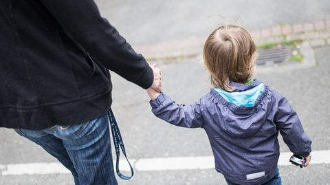Ein Mann in Jeans und schwarzer Jacke ist mit seinem blonden Kind an der Hand von hinten zu sehen