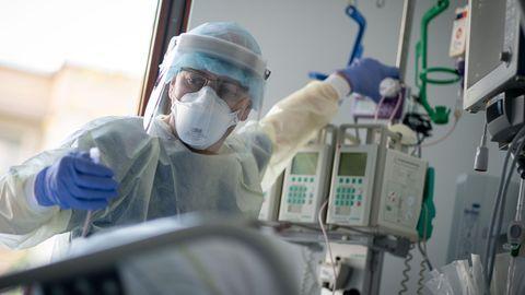 Ein Mann in hellblauer medizinischer Schutzkleidung und Gesichtsschild überprüft die Monitore an einem Intensivbett