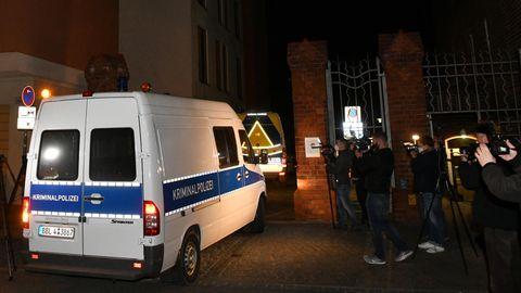 """Ein weißer Mercedes Sprinter mit blauem Streifen und """"Kriminalpolizei""""-Beschriftung fährt im Dunkeln durch ein Backstein-Portal"""