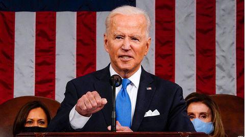 Ein weißhaariger weißer Mann steht im Anzug an einem hölzernen Redepult und macht mit der rechten Hand eine Faust