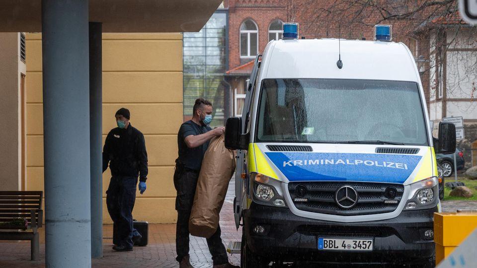 Ein Mitarbeiter der Kriminalpolizei bringt Gegenstände auf dem Gelände eines Potsdamer Wohnheimesin ein Polizeiauto. In dem Wohnheimsind vier Leichen gefunden worden.