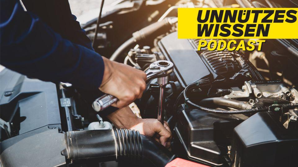 Hände werkeln unter einer Motorhaube