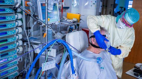 Eine Krankenpflegerin setzt einem Patienten eine Beatmungsmaske auf.