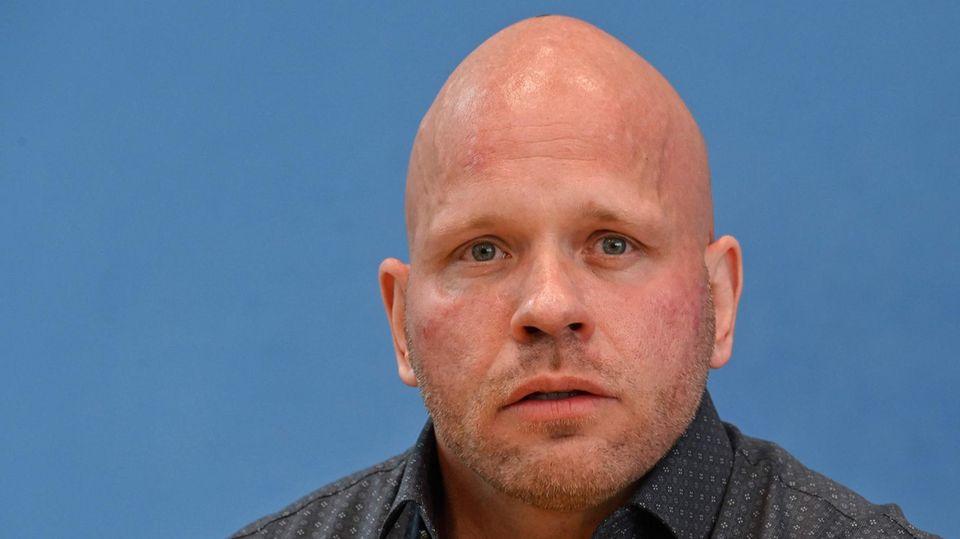 Ein muskulöser, glatzköpfiger weißer Mann sitzt in grauem Hemd mit hellen Punkten vor einer blauen Wand