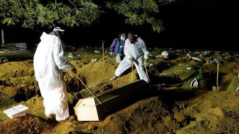 Zwei Menschen in weißen Schutzanzügen senken auf einem dunklen Friedhof einen hellen Holzsarg in eine Grube