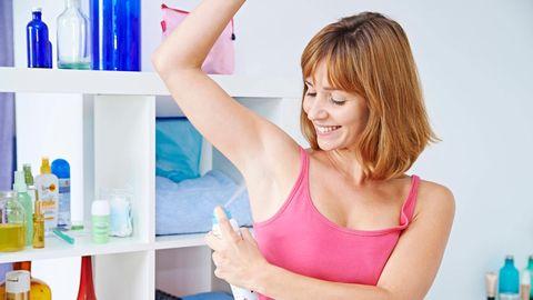 Frau trägt Deodorant auf.